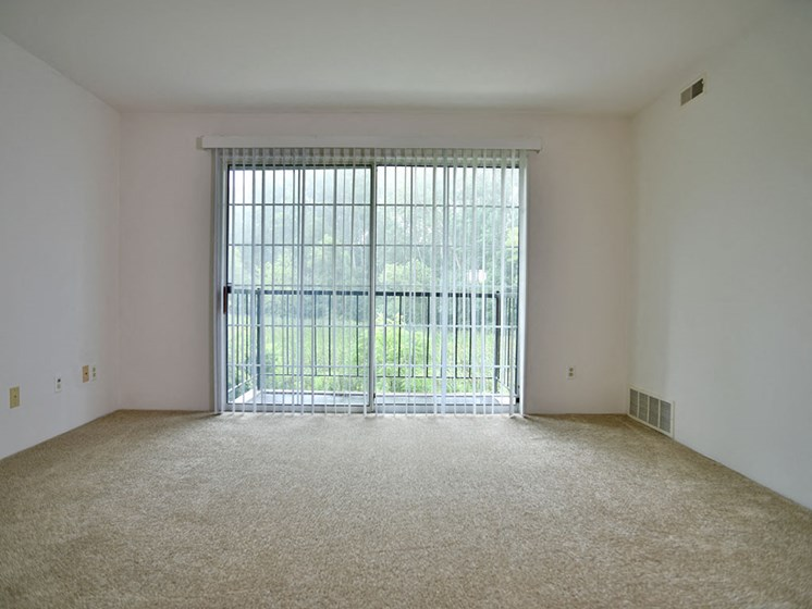 Living Room With Balcony Access at Charter Oaks Apartments, Davison, MI