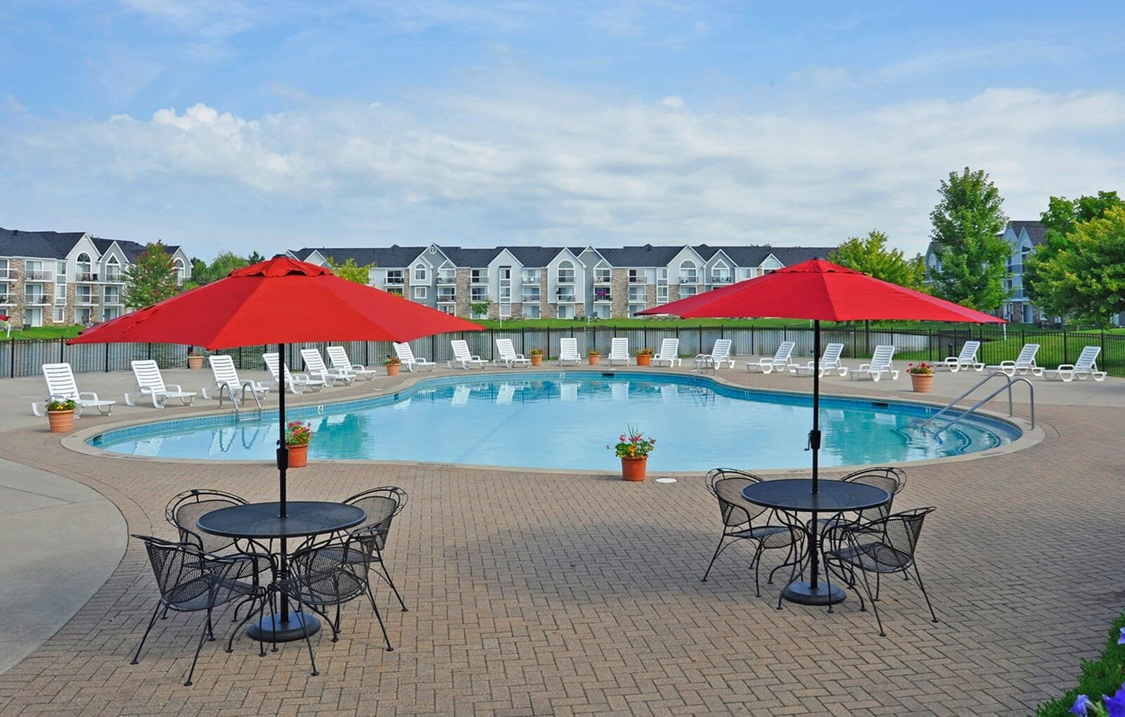 Umbrella Shaded Chairs by Pool at Southport Apartments, Belleville, MI