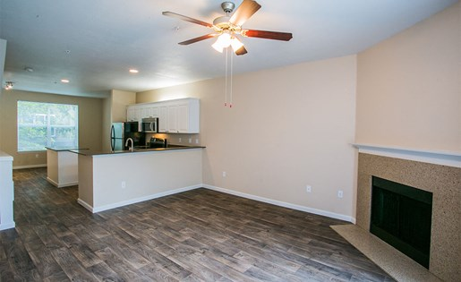 Spacious Model Living Room with Faux Wood Floors and Brick Wood-Burning Fireplace in Apartment Near Orenco