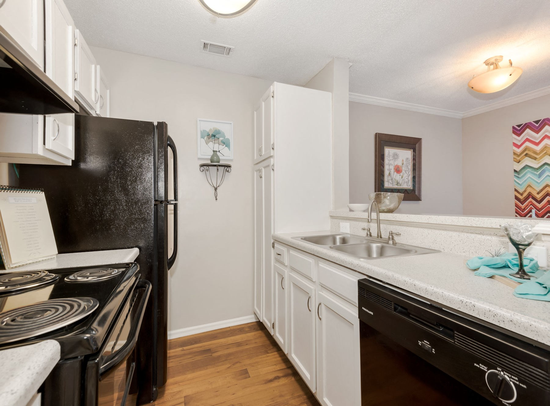 Model Kitchen With White Cabinets & Black Appliances