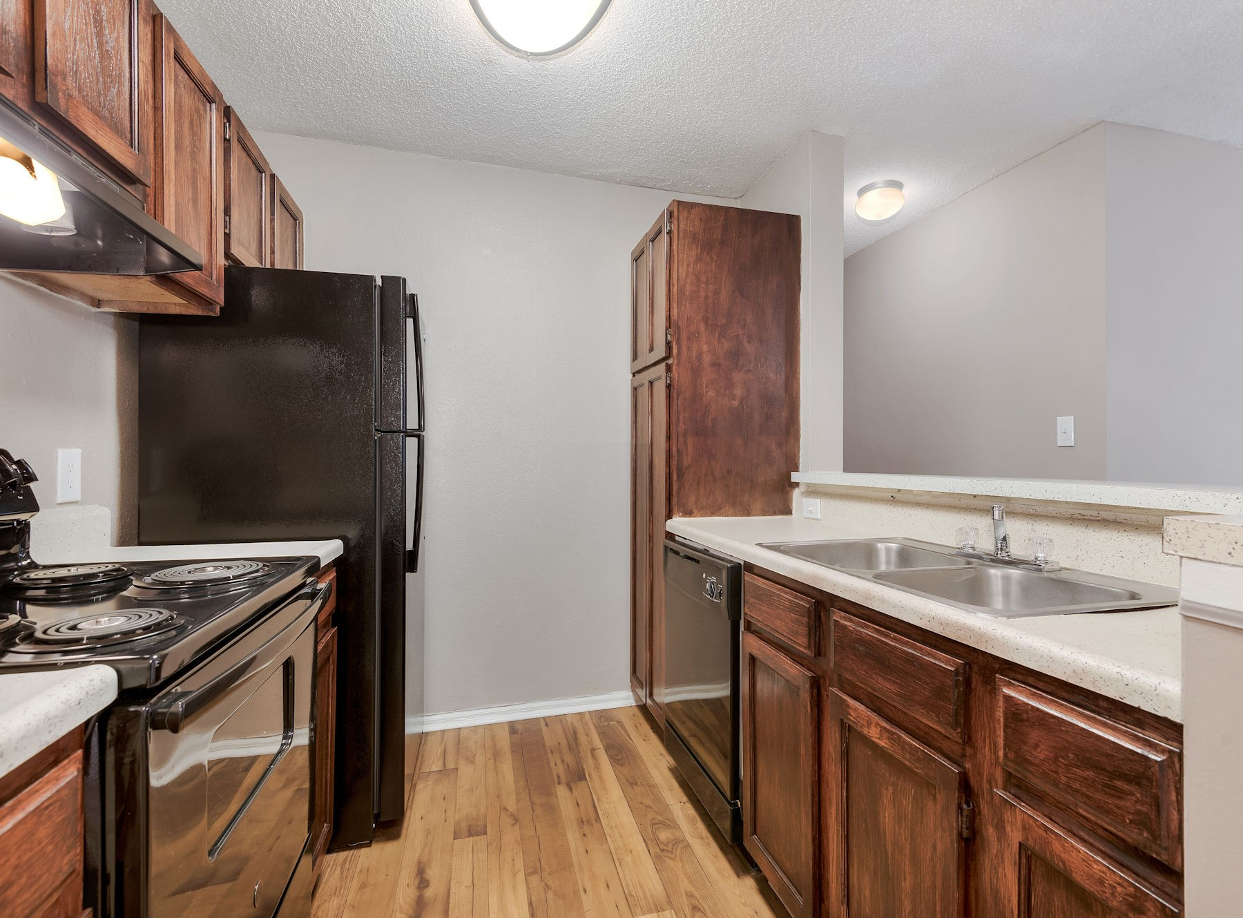 Model Kitchen With Wood Cabinets & Black Appliances