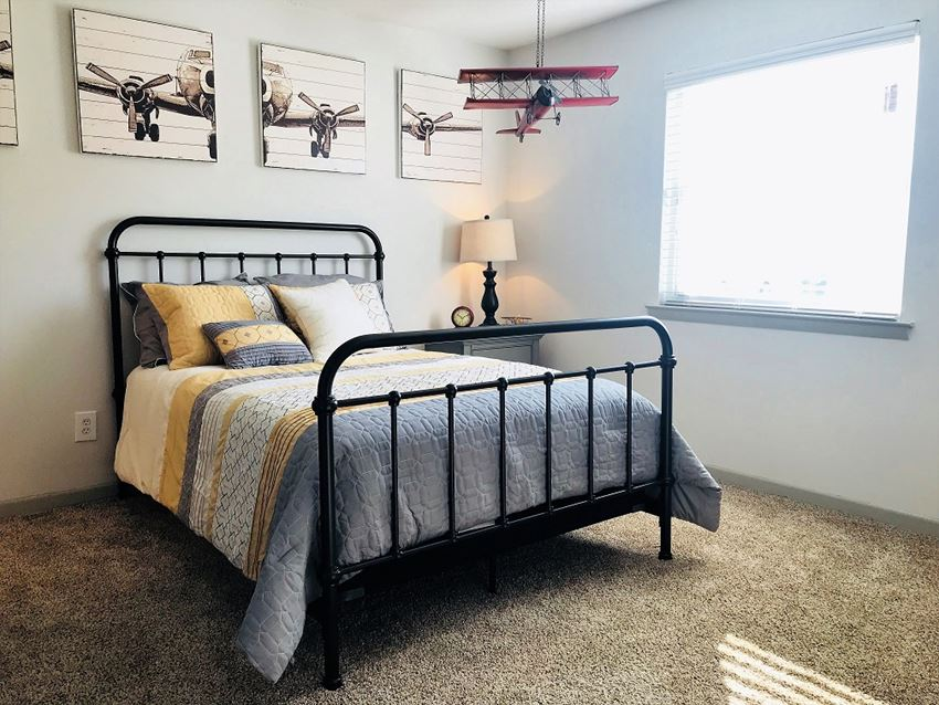 Bed with a white, yellow, and gray colored spread in a carpeted room and a model airplane hanging from the ceiling