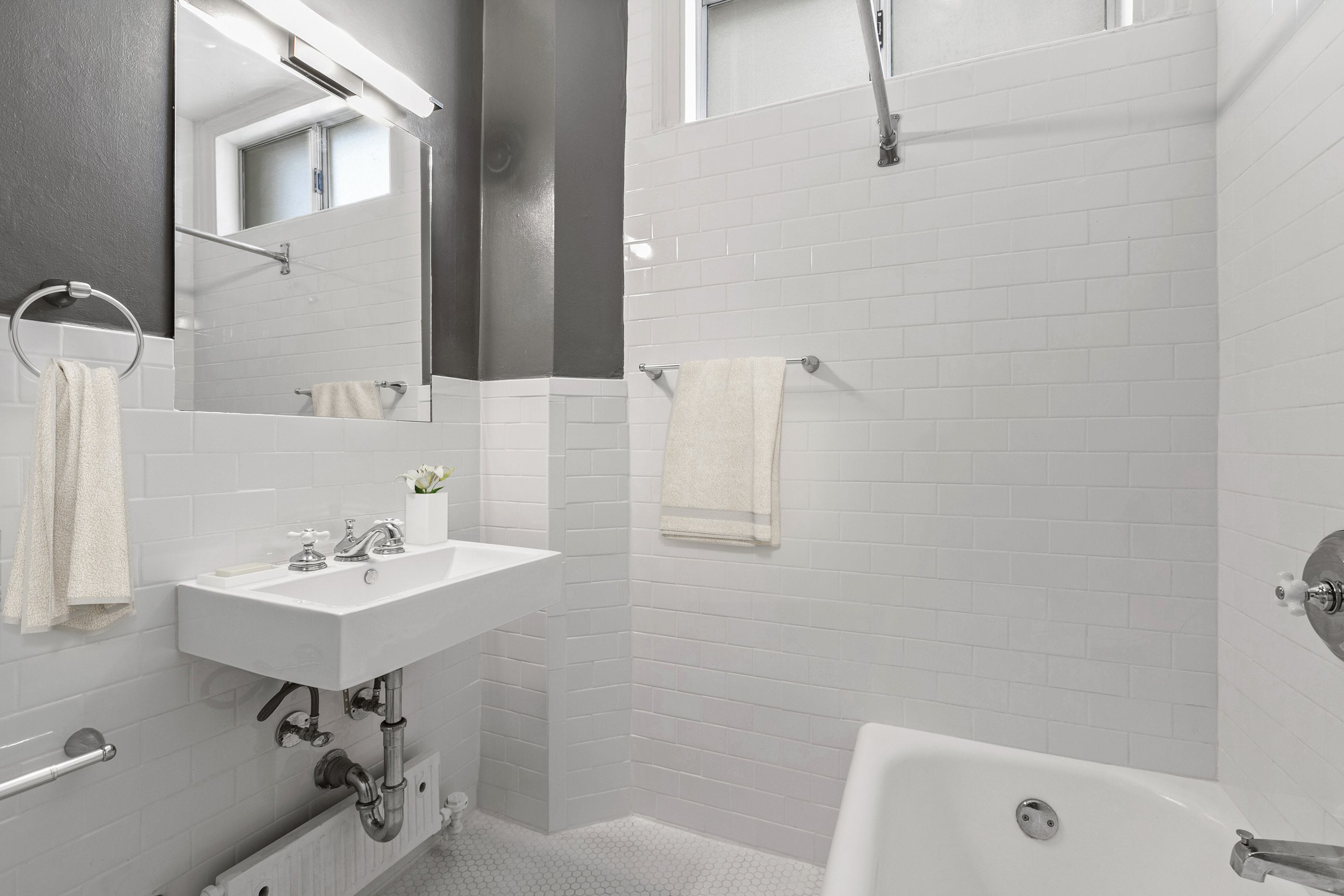 Apartments in Westlake-Wilshire Royale Bathroom with Stylish White Tile, Spacious Countertops, and Large Shower Area
