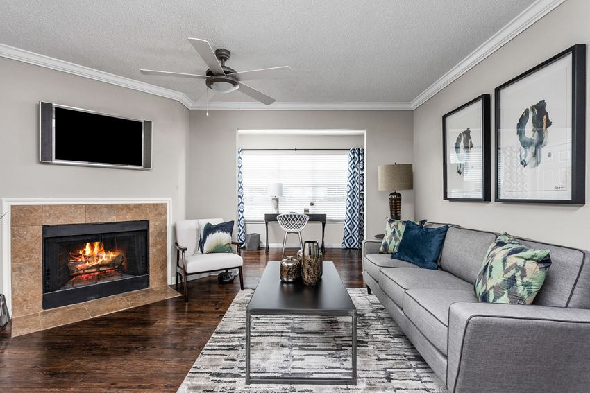 Apartment living room with fireplace, hardwood floors, and ceiling fan
