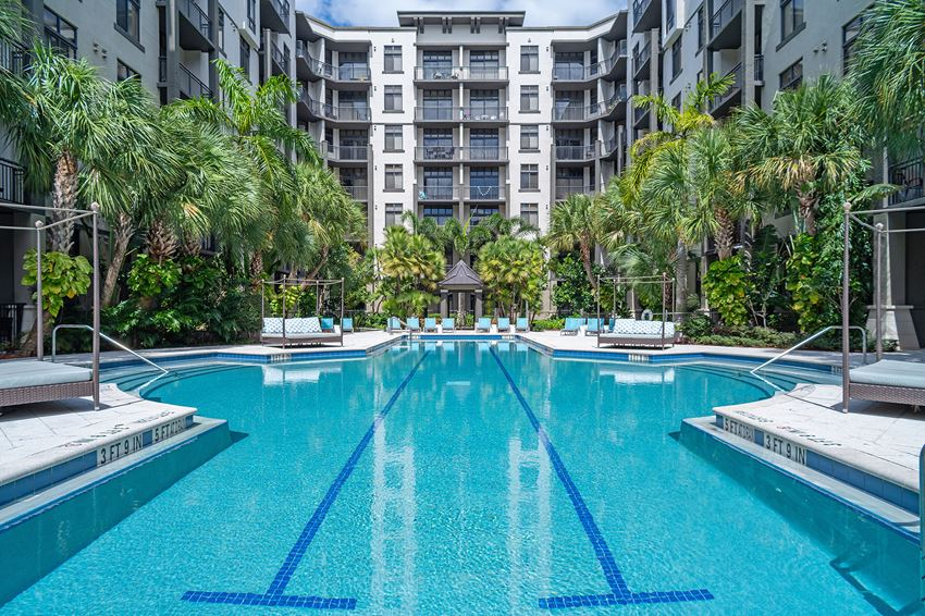 Lap pool surrounded by lounge chairs, cabanas, and mid-rise apartment building