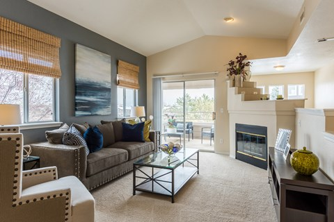 Living area with windows, fireplace, and sliding glass doors to patio