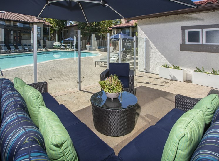 Seating area adjacent to pool with glass partition fence