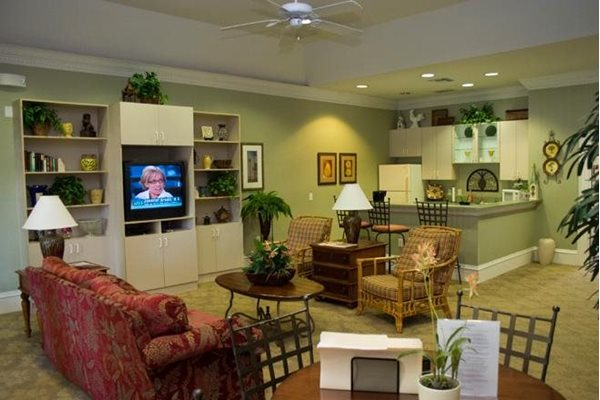 community clubhouse with tv, fireplace, and kitchen at whispering woods apts in st augustine fl