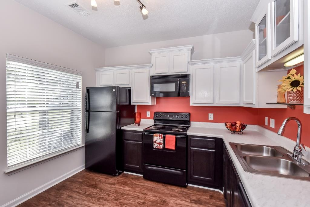 Upgraded unit interior featuring espresso custom cabinetry with crown molding, black appliances w/ microwave, new countertops, lighting package, gooseneck faucets with sprayer, rainwater shower heads, premium wood blinds, and wood-style plank flooring.