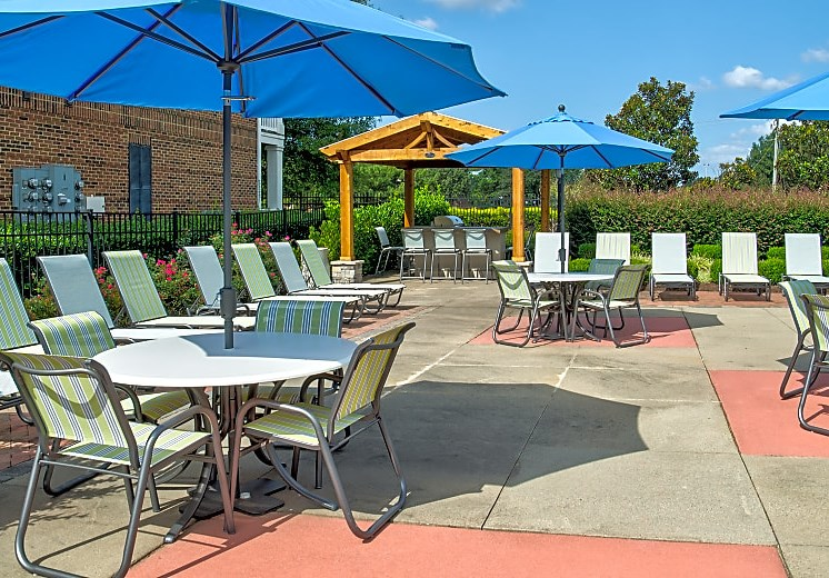 deck chairs and picnic tables with open umbrellas on pool deck