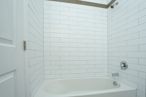Bathtub in bathroom with white tile walls
