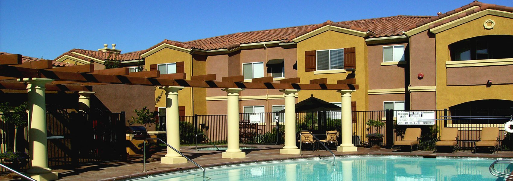 Pool with apt buildings in back  Elk Grove Apartments l Castellino at Lauga West Apartments