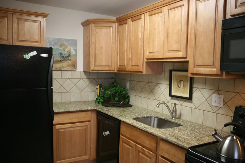 Kitchen with granite counter tops, black appliances and tile backslash