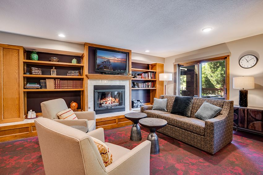 Clubroom with conversational seating in front of a fireplace and a TV