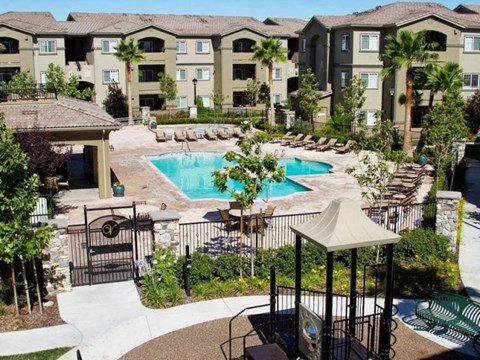 Pool with lounge chairs l The Villas at Villaggio Apartments in Modesto CA