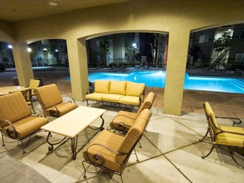 Seating by pool l The Villas at Villaggio Apartments in Modesto CA