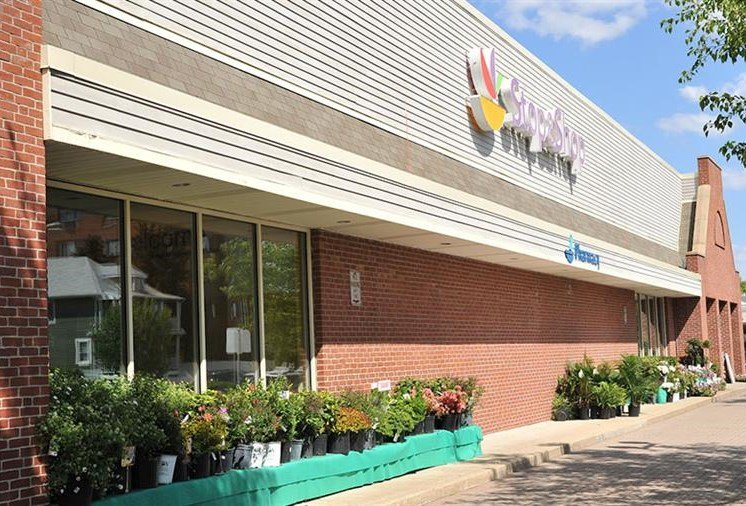 Stop N Shop grocery store with plants for sale in front and customers walking near by - luxury Arlington mass apartments
