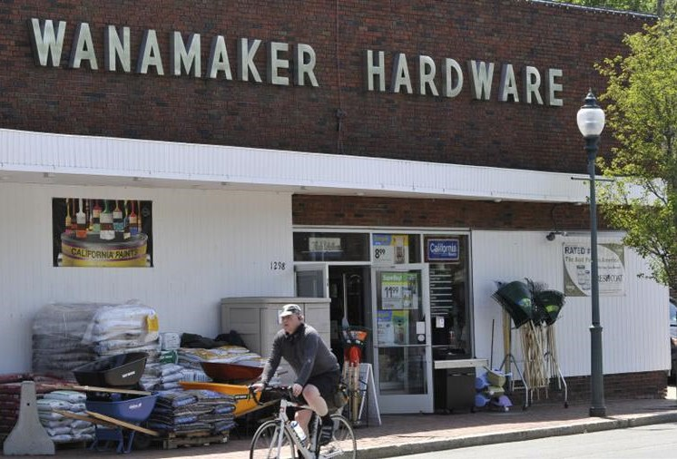 wanamaker hardware store with items for sale out front and man on bicycle riding by - luxury arlington ma apartments