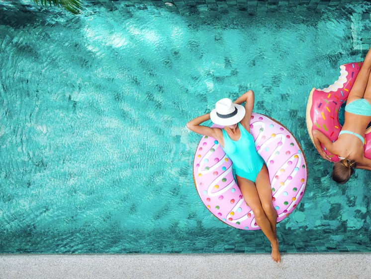 2 women in swimming pool laying on donut shaped pool floats