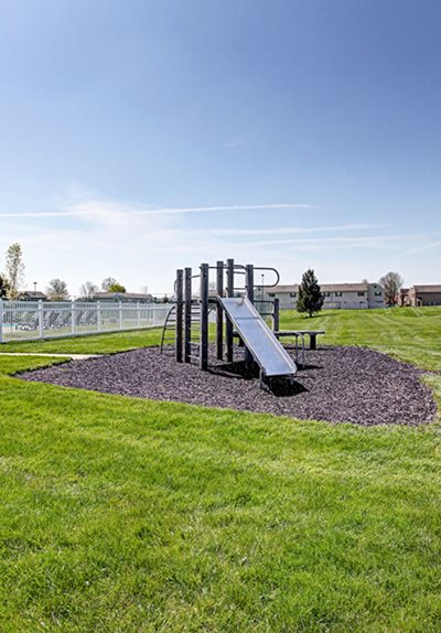 Playground surrounded by grassy area at Worthington Meadows Townhomes in Columbus, Ohio 43085