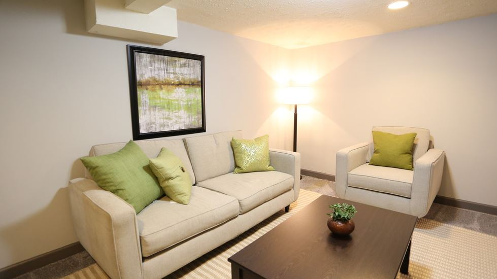 Finished basement with hardwood flooring, sofa, chairs, and coffee table at Worthington Meadows Townhomes in Columbus, Ohio 43085