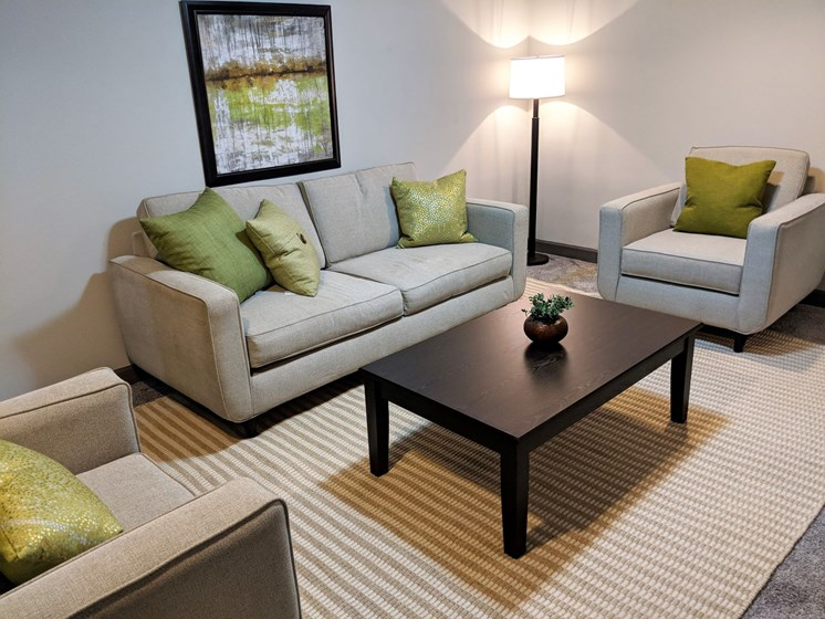 Finished basement with sofas, coffee table and hardwood flooring at Worthington Meadows Townhomes in Columbus, Ohio 43085