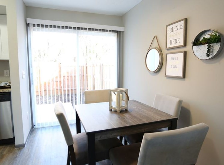 View of dining room area with hardwood flooring and sliding door leading to private fenced patio at Worthington Meadows Townhomes in Columbus, Ohio 43085