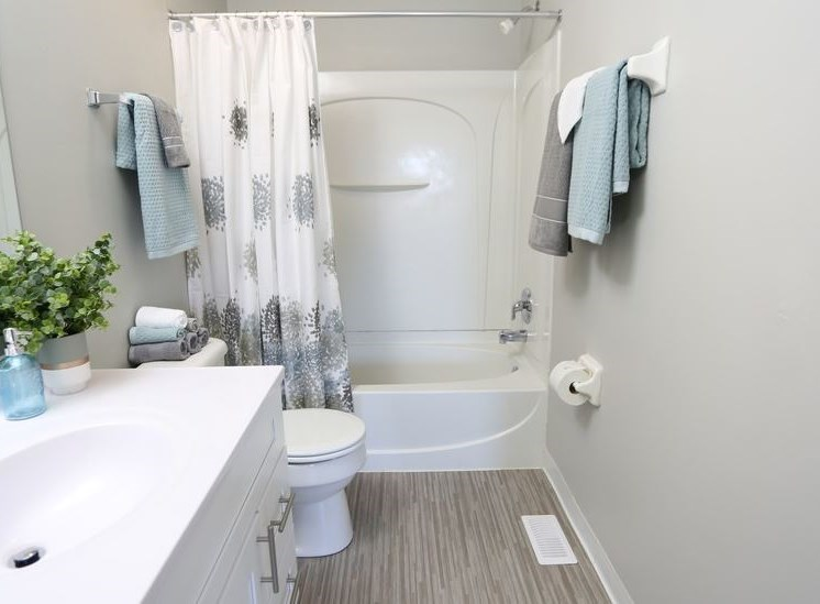 Full bathroom with hardwood flooring, bathtub, toilet, towel bars, large sink area with mirror and cabinet at Worthington Meadows Townhomes in Columbus, Ohio 43085