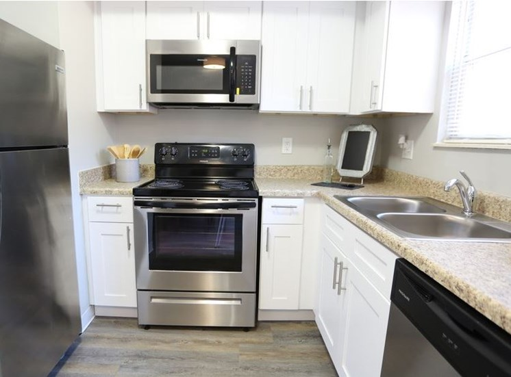 Modern fulyl-equipped kitchen with stainless steel appliances, granite countertops, white cabinets, and window at Worthington Meadows Townhomes in Columbus, Ohio 43085