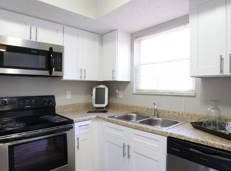 Modern fully-equipped kitchen with stainless steel appliances, white cabinets, granite countertops, and large window at Worthington Meadows Townhomes in Columbus, Ohio 43085