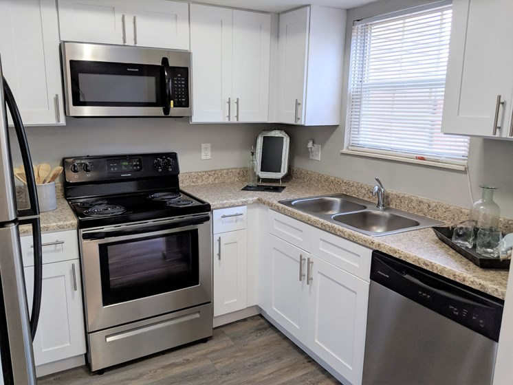 Modern fully-equipped kitchen with stainless steel appliances and white cabinets at Worthington Meadows Townhomes in Columbus, Ohio 43085
