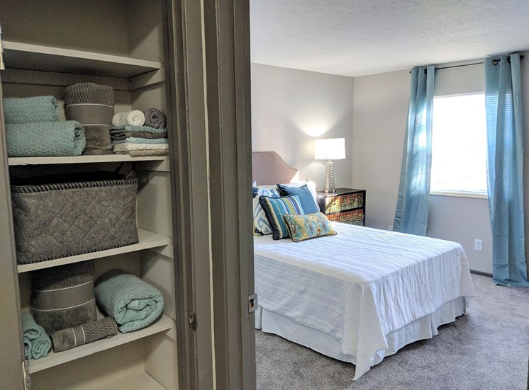 View of extra storage linen closet with shelving, and bedroom with carpeting and windows at Worthington Meadows Townhomes in Columbus, Ohio 43085