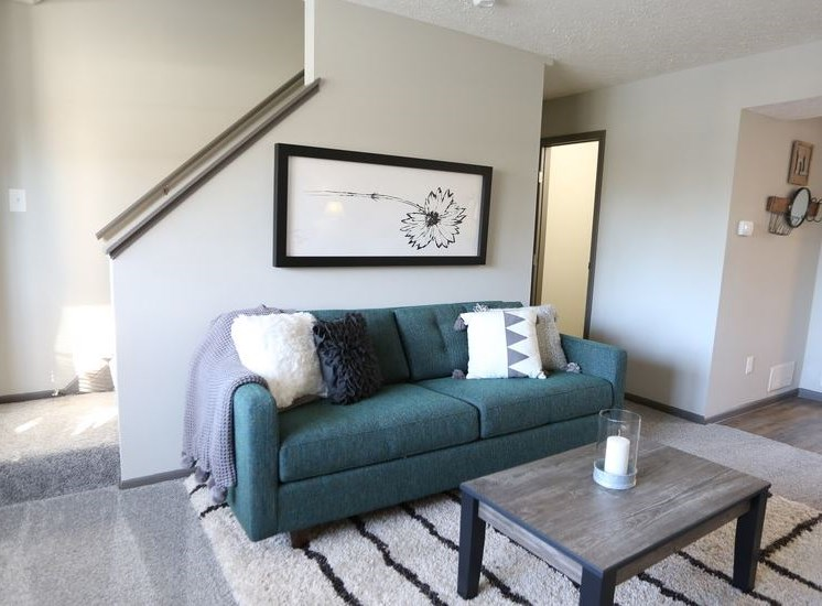 Brightly lit living room with carpeting and stairs along the wall leading upstairs at Worthington Meadows Townhomes in Columbus, Ohio 43085