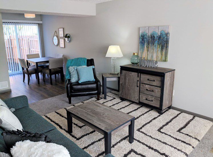 Open floor concept of living and dining areas featuring carpeting and hardwood flooring and sliding door at Worthington Meadows Townhomes in Columbus, Ohio 43085