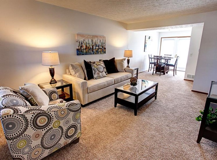 View of open floor concept of living and dining areas with carpeting, sliding door to patio, and hardwood flooring at Worthington Meadows Townhomes in Columbus, Ohio 43085