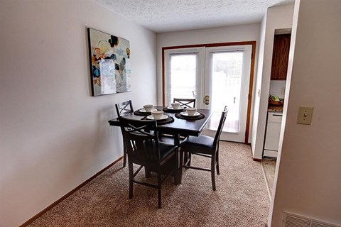 Dining room area with tile flooring and sliding glass door leading to private fenced patio at Worthington Meadows Townhomes in Columbus, Ohio 43085