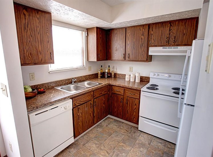 L-shaped kitchen with wood cabinets, stainless steel sink, range, refrigerator, dishwasher, and window at Worthington Meadows Townhomes in Columbus, Ohio 43085