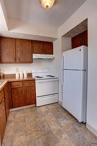 Kitchen area featuring refrigerator, range, tile flooring, and wood cabinets at Worthington Meadows Townhomes in Columbus, Ohio 43085