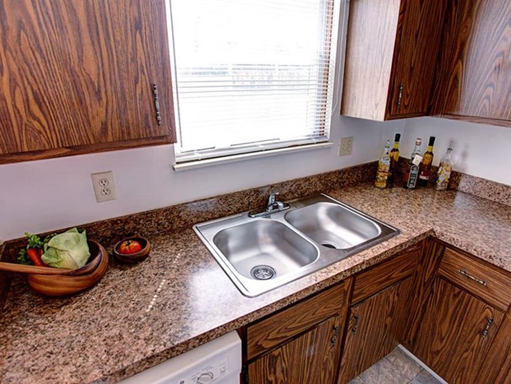 Kitchen area featuring stainless steel sink, granite countertops, and wood cabinets at Worthington Meadows Townhomes in Columbus, Ohio 43085
