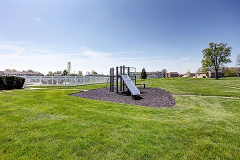 Playground surrounded by large grassy area at Worthington Meadows Townhomes in Columbus, Ohio 43085