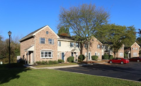 View of exterior of townhomes and parking lot in front of building at Worthington Meadows Townhomes in Columbus, Ohio 43085