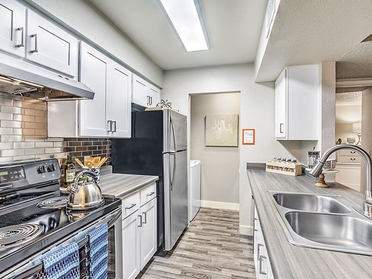 Kitchen With Stainless Steel Appliances, Sleek Cabinetry and Chic Tile Backsplash