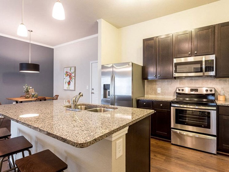Fully-Equipped Kitchen With Wood Flooring at Creekside at Greenlawn Apartments in Columbia, SC