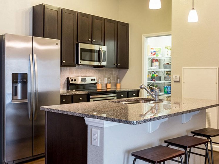 Kitchen With Marble Countertops and Pantry Space at Creekside at Greenlawn Apartments in Columbia, SC