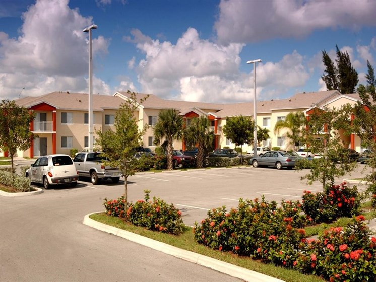 apartment building exterior with cars in parking lot_Douglas Pointe Apartments Carol City, FL