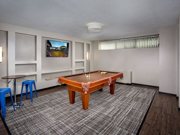 game room at Cole Spring Plaza apartments in downtown Silver Spring MD with pool table, seating area and wall-mounted TV