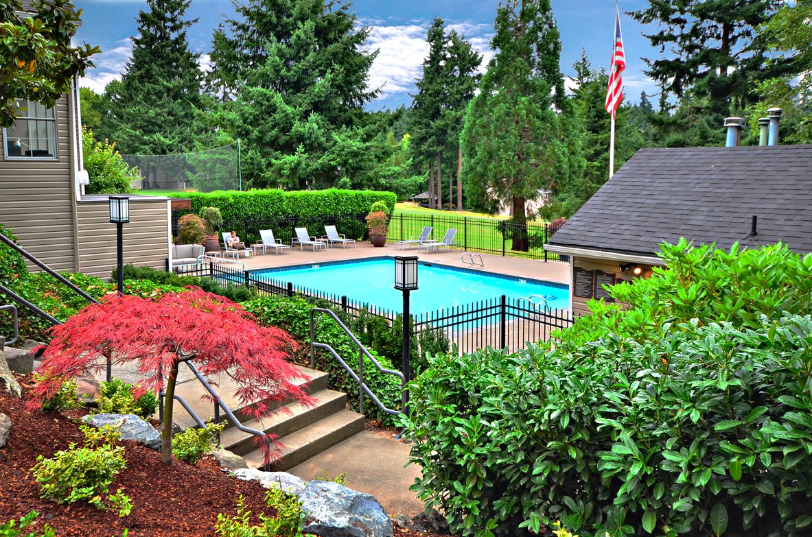 Tacoma WA Apartments-The Fairways Apartments Swimming Pool Surrounded by Lush Landscape and Lounge Chairs