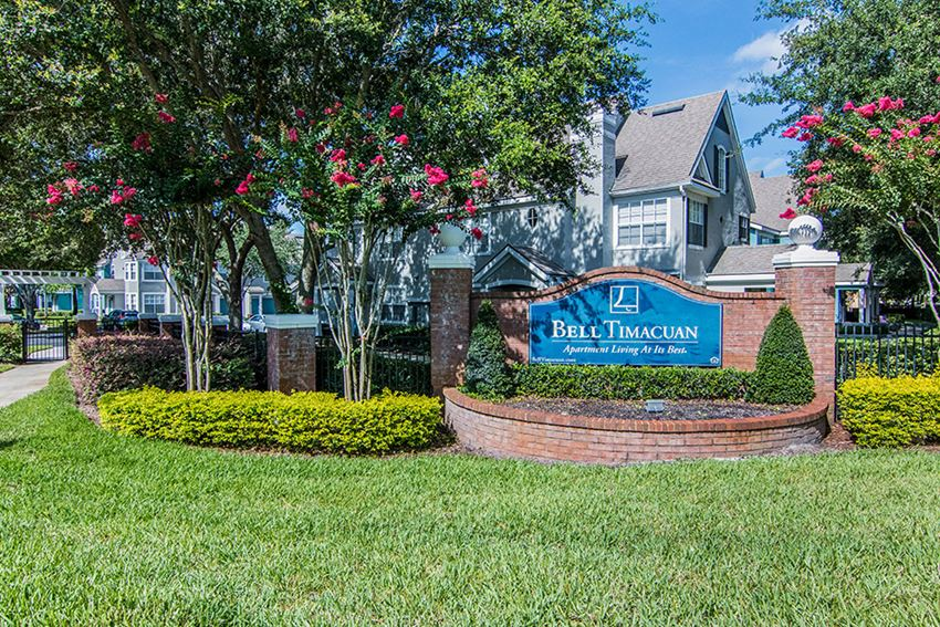 Brick entrance sign of apartment community with lush landscaping