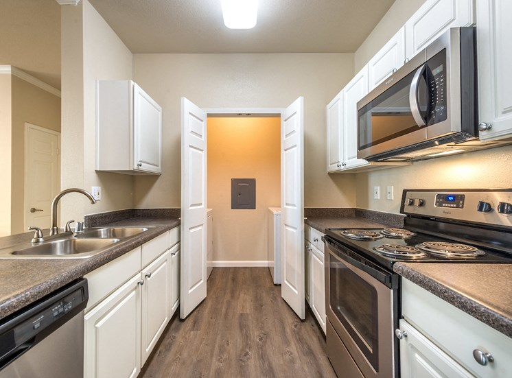 Kitchen with adjacent washer and dryer room