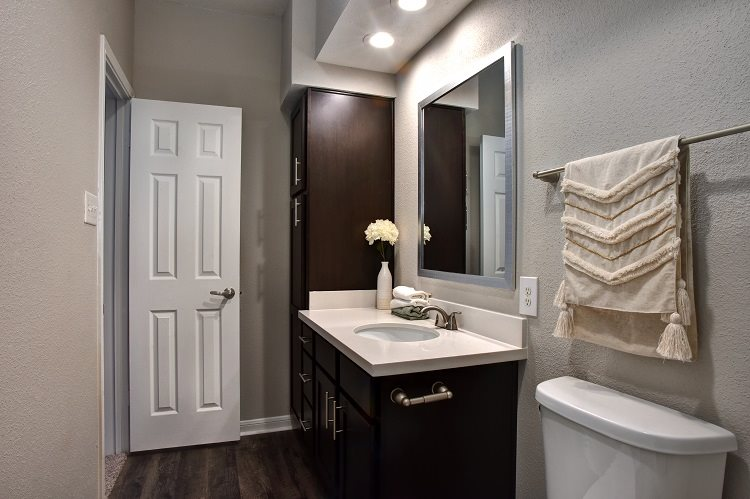 Master bathroom with floating vanities, quartz countertops, backlit vanity mirror, walk-in shower with Euro shower door and quartz-topped bench seat at Greenbriar Park, Texas, 77030
